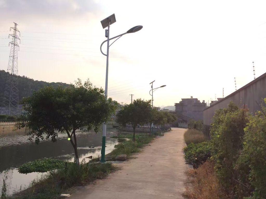 村庄,宽阔的水泥路途穿行全村,水泥路上的太阳能路灯反射出耀眼的光辉图片